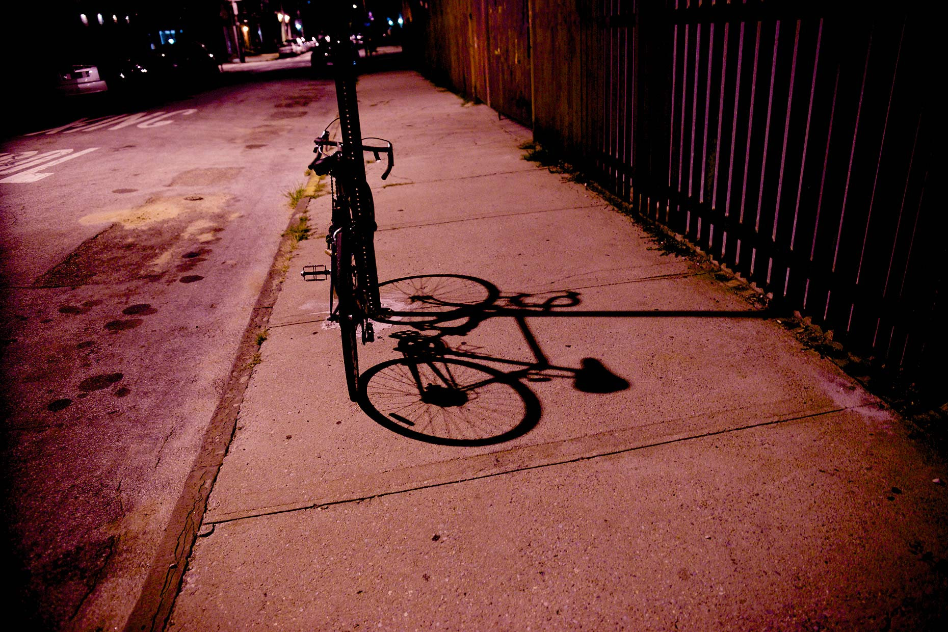 Bike leaning on post on Red Hook Brooklyn street late at night casting shadow