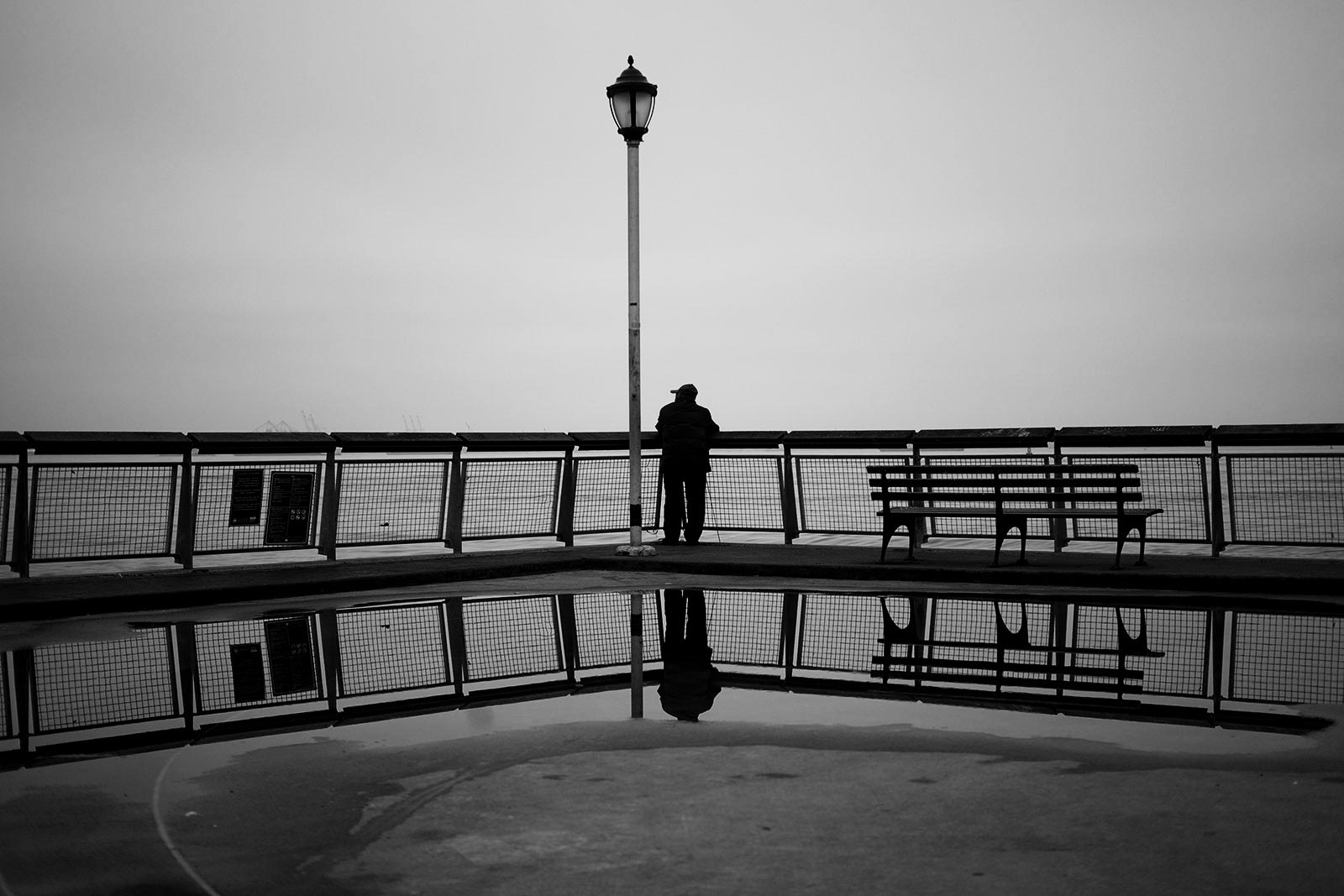 man-at-railing-on-harbor-in-fog